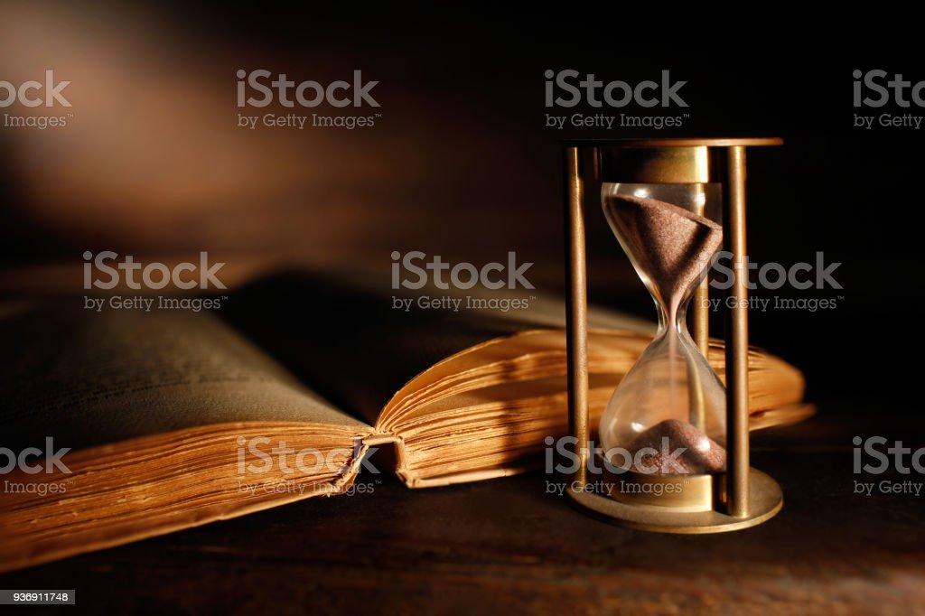 vecchia clessidra e libro antico stock photo