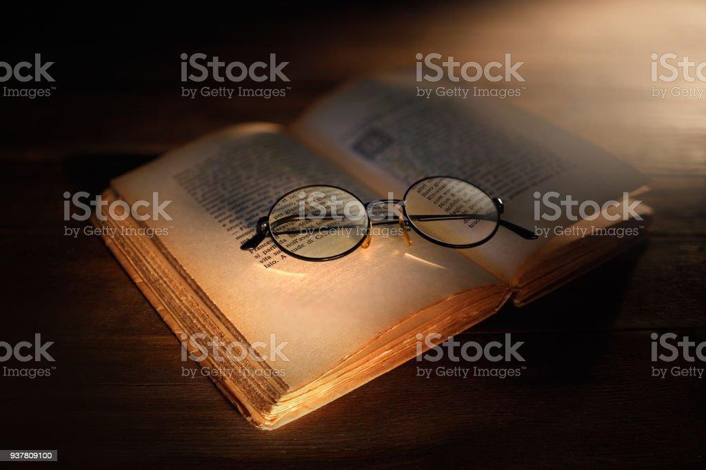 vecchio libro aperto con occhiali antichi stock photo