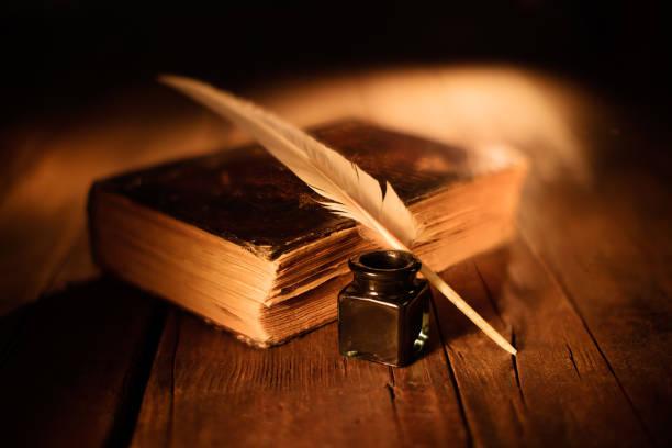 vecchio libro con penna d'oca e calamaio vecchio libro con penna d'oca e calamaio su tavolo di legno libro stock pictures, royalty-free photos & images