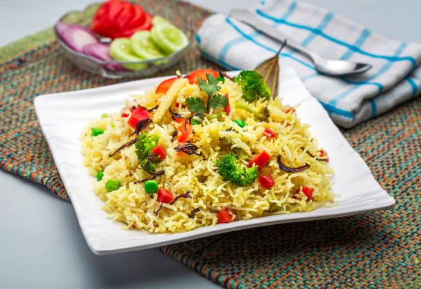 veg biryani or veg pulav or steamed rice a plate full of vegetable pulav or veg biryani or steamed rice or cooked rice with salad basmati rice stock pictures, royalty-free photos & images