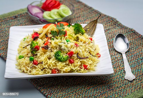a plate full of vegetable pulav or veg biryani or steamed rice or cooked rice with salad