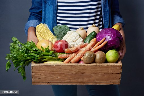 Studio shot of an unrecognizable woman holding a wooden crate full of fruit and vegetables against a blue background