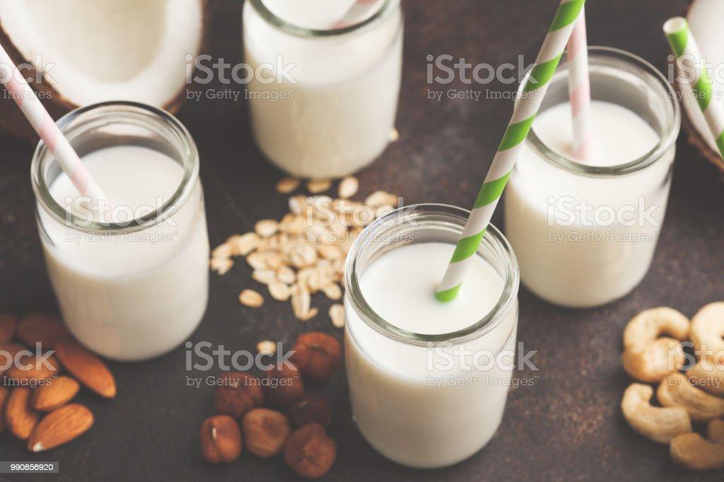 Vegan alternative nut milk in glass bottles on dark background....