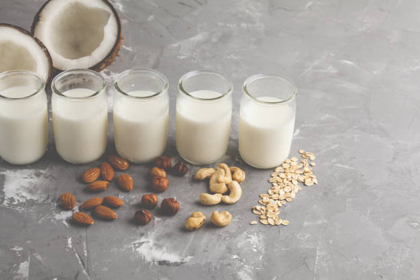 Vegan alternative nut milk in glass bottles on gray background. Healthy vegan food concept. stock photo