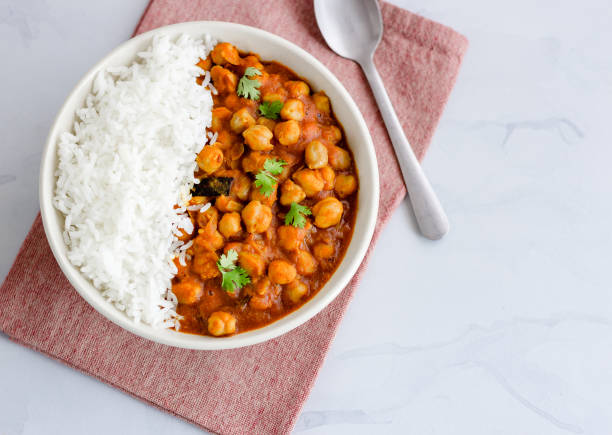 Vegan and Low Carb Chickpea Curry and Rice Vegan and Low Carb Chickpea Curry with Rice in a Bowl Directly Above Photo. Healthy Indian Chickpea Curry. curry powder stock pictures, royalty-free photos & images