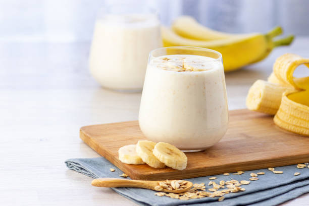Vegan banana and oatmeal smoothie in glass jar on the light background. Vegan banana and oatmeal smoothie in glass jar on the light background. Healthy food. banana stock pictures, royalty-free photos & images