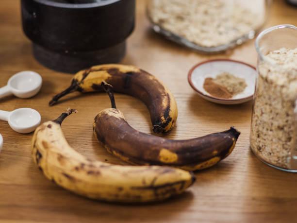vegane bananenbrot und zutaten mit über reife bananen - gebackene banane stock-fotos und bilder