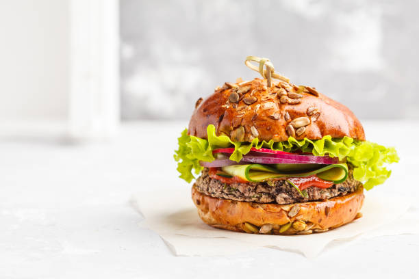 Vegan bean burger with vegetables and tomato sauce, copy space, white background. Healthy vegan food concept. stock photo