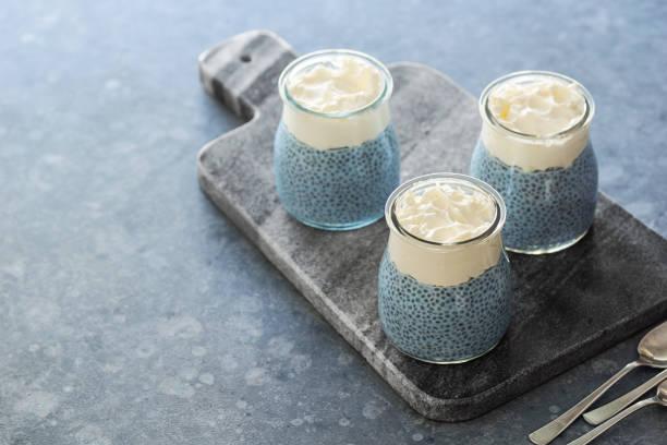 vegane blau spirulina chia pudding mit schlagsahne kokos-creme - portugiesische desserts stock-fotos und bilder