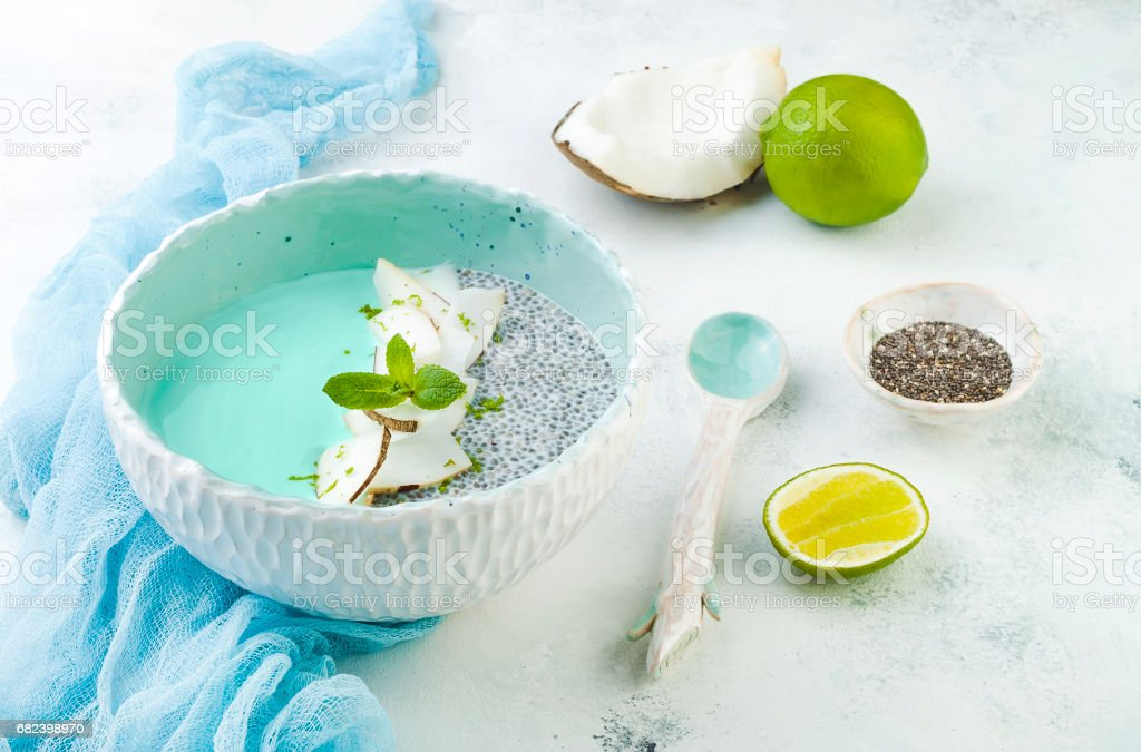 Vegan blue spirulina smoothie and chia pudding bowl topped with coconut flakes and lime royalty-free stock photo
