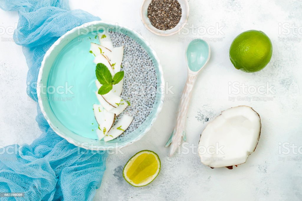 Vegan blue spirulina smoothie and chia pudding bowl topped with coconut flakes and lime photo libre de droits