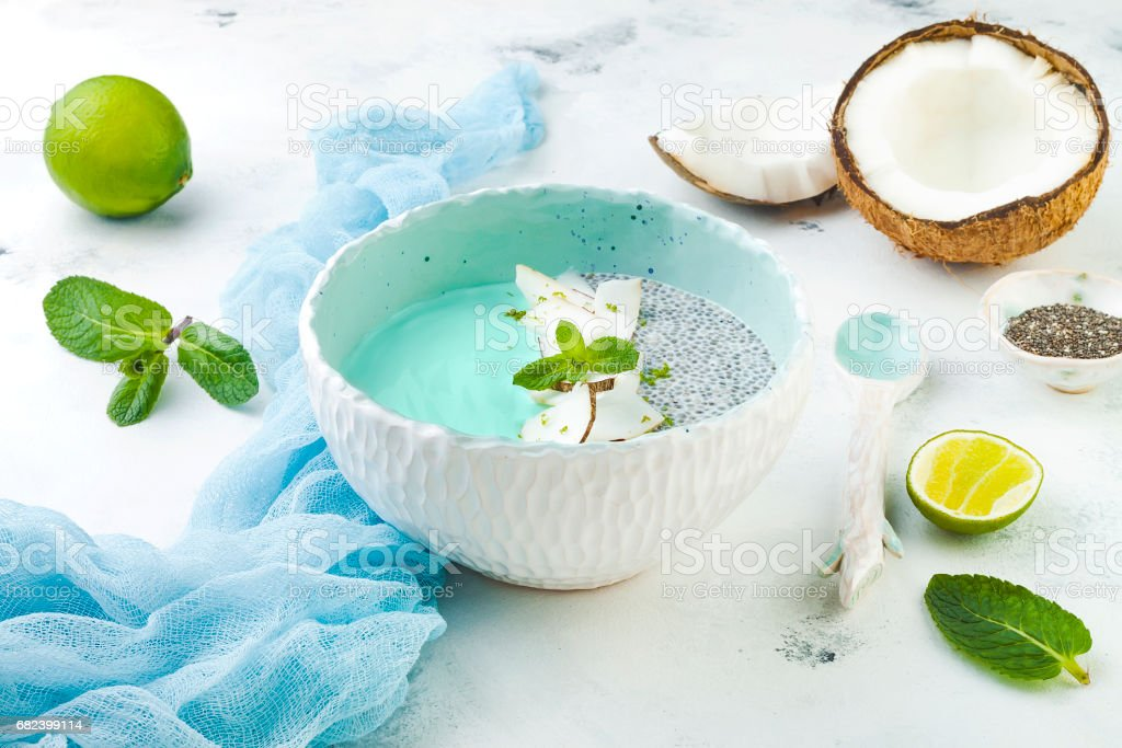 Vegan blue spirulina smoothie and chia pudding bowl topped with coconut flakes and lime stock photo