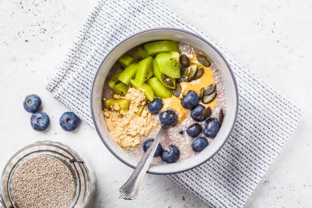 veganes frühstück. chia pudding mit kiwi, heidelbeeren und erdnussbutter, ansicht von oben. - chia pudding kokosmilch stock-fotos und bilder