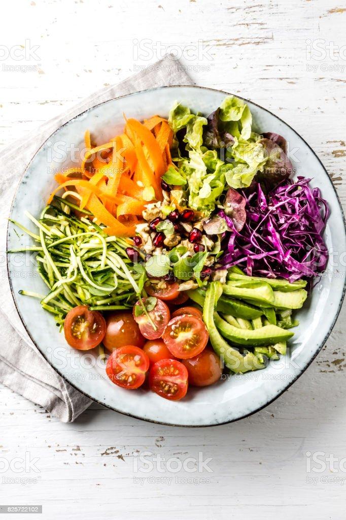 Bol de Vegan de Bouddha. Bol avec crudités - chou, carotte, courgette, laitue, salade de cresson, cerise tomates et avocat, noix et Grenade - Photo