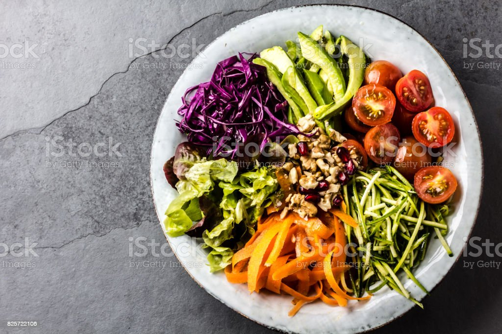 Vegan buddha bowl. Bowl with fresh raw vegetables - cabbage, carrot, zucchini, lettuce, watercress salad, tomatoes cherry and avocado, nuts and pomegranate stock photo
