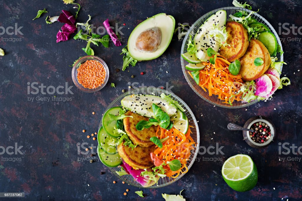 Vegan buddha bowl dinner food table. Healthy food. Healthy vegan lunch bowl. Fritter with lentils and radish, avocado, carrot salad. Flat lay. Top view stock photo