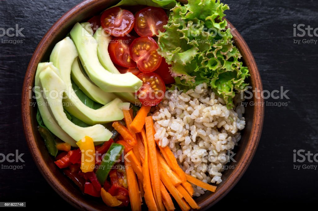 Vegan buddha bowl on black background. Top view. Bowl with carrot, lettuce, tomatoes cherry, pepper, avocado and porridge. Vegetarian, healthy, detox food concept. stock photo