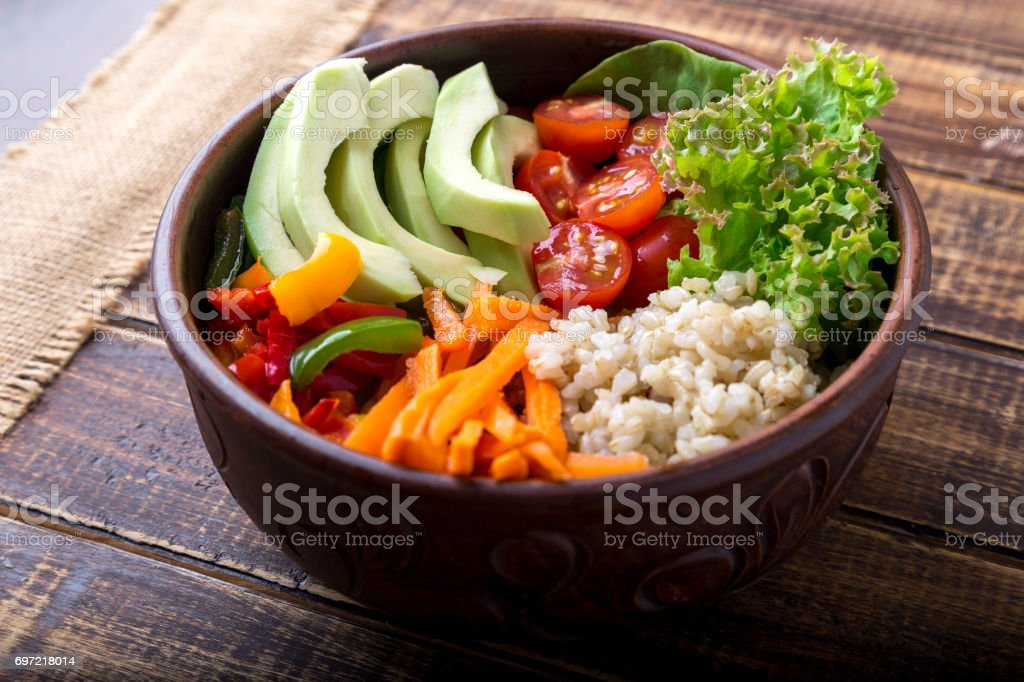 Vegan buddha bowl on wooden background. Bowl with carrot, lettuce, tomatoes cherry, pepper, avocado and porridge. Vegetarian, healthy, detox food concept. stock photo