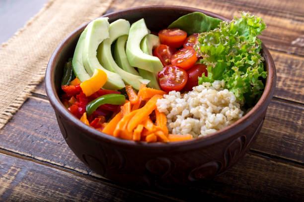 Bol de Bouddha végétalien sur fond en bois. Bol avec le jus de carotte, laitue, tomates cerises, poivron, avocat et bouillie. Végétarienne, saine, concept alimentaire de désintoxication. - Photo