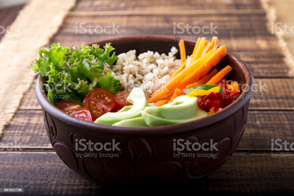 Vegan buddha bowl on wooden background. Top view. Bowl with carrot, lettuce, tomatoes cherry, pepper, avocado and porridge. Vegetarian, healthy, detox food concept. stock photo