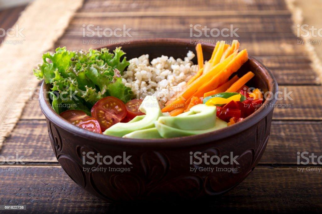 Bol de Bouddha végétalien sur fond en bois. Vue de dessus. Bol avec le jus de carotte, laitue, tomates cerises, poivron, avocat et bouillie. Végétarienne, saine, concept alimentaire de désintoxication. - Photo