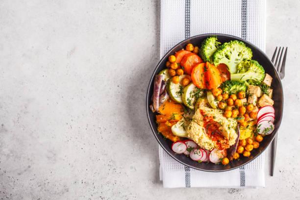 vegan buddha bowl with baked vegetables, chickpeas, hummus and tofu, top view. - dieta macrobiotica foto e immagini stock
