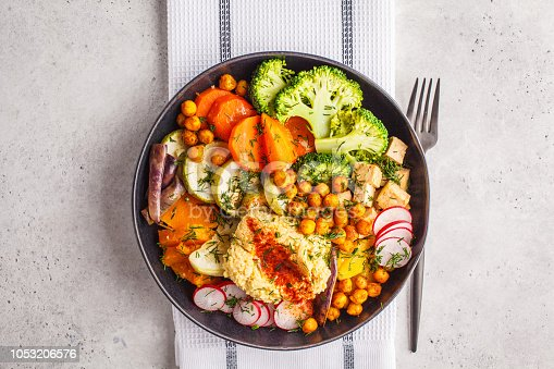 Vegan Buddha bowl with baked vegetables, chickpeas, hummus and tofu on white background. Detox, Clean eating concept.