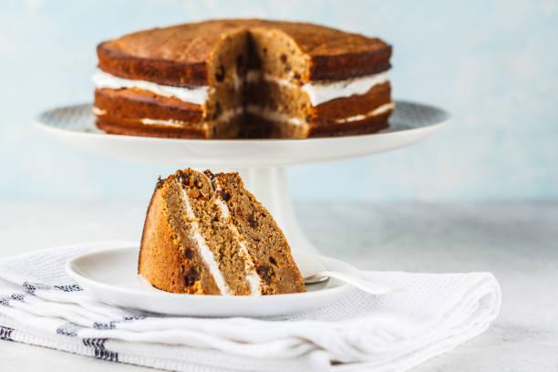 veganer karottenkuchen mit kokoscreme, weißer hintergrund. - paleo kuchen stock-fotos und bilder