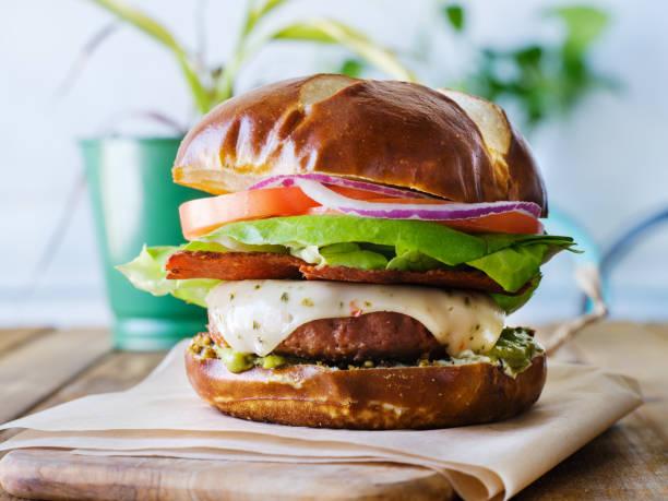 Hamburger au fromage végétalien sur petit pain bretzel et bacon sans viande - Photo