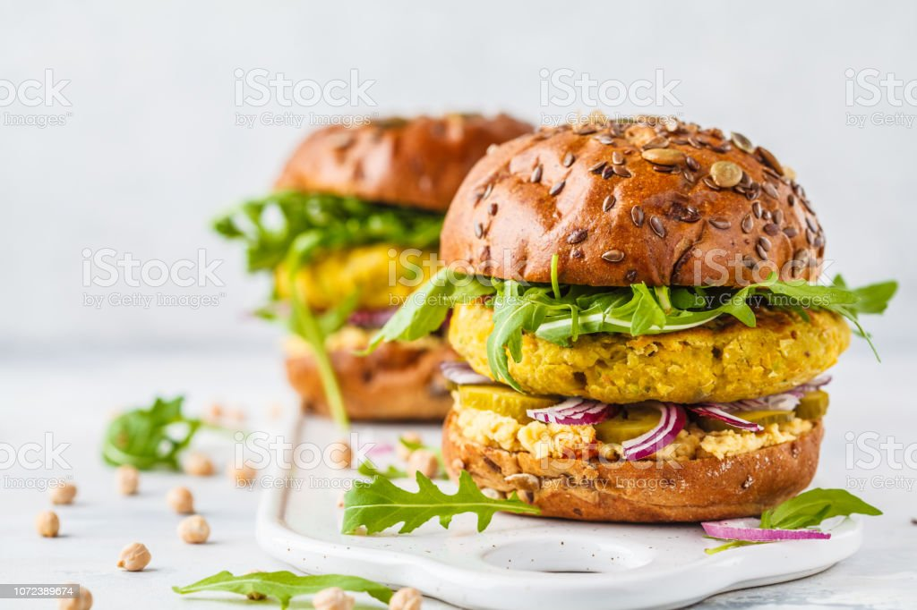Vegan chickpeas burgers with arugula, pickled cucumbers and hummus, copy space. stock photo
