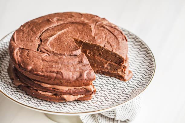 vegane schokolade kuchen auf einem weißen teller für kuchen, textfreiraum, heller hintergrund. - paleo kuchen stock-fotos und bilder