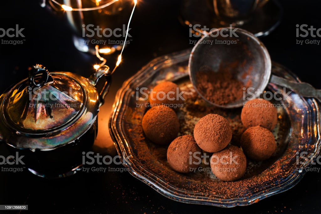 vegan chocolate truffles - dessert for the New Year's Eve, carnival against the background of silverware, elegant, vintage. On a dark background. stock photo