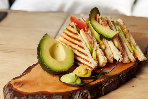 Vegan Club Sandwich with avocado on wooden tray stock photo