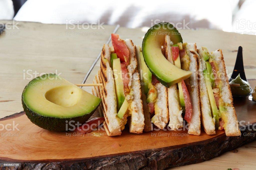 Vegan Club Sandwich with avocado on wooden tray stock photo