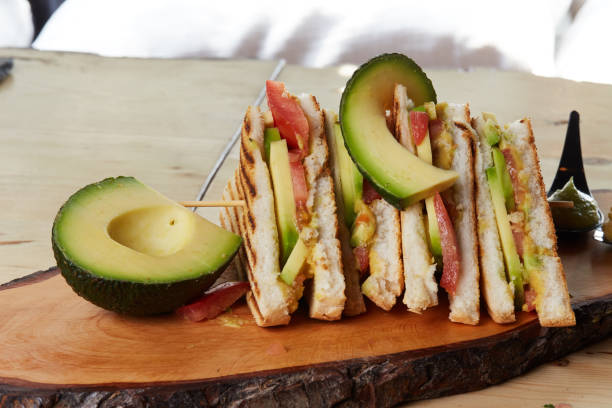 vegan club sandwich with avocado on wooden tray - club sandwich stock photos and pictures