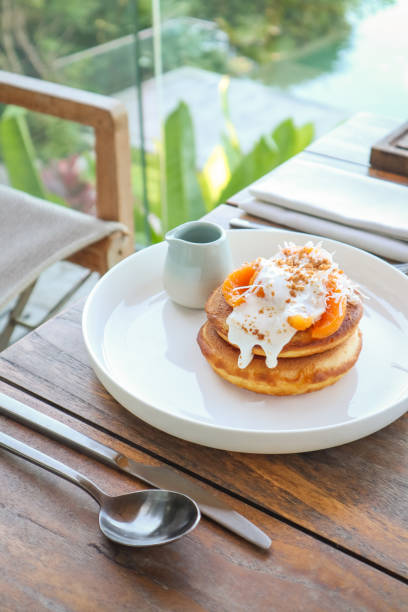 Vegan Coconut Banana Pancakes with Mango at tropical Breakfast Table stock photo