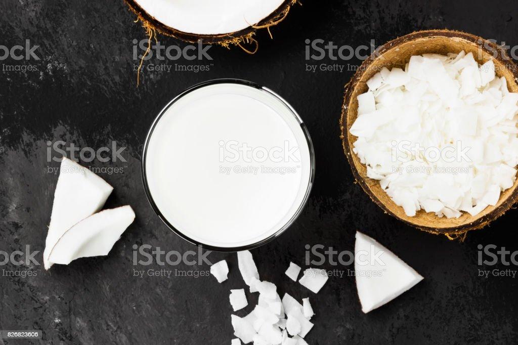 Vegan coconut milk in glass on a dark background. Non-dairy milk. Top...