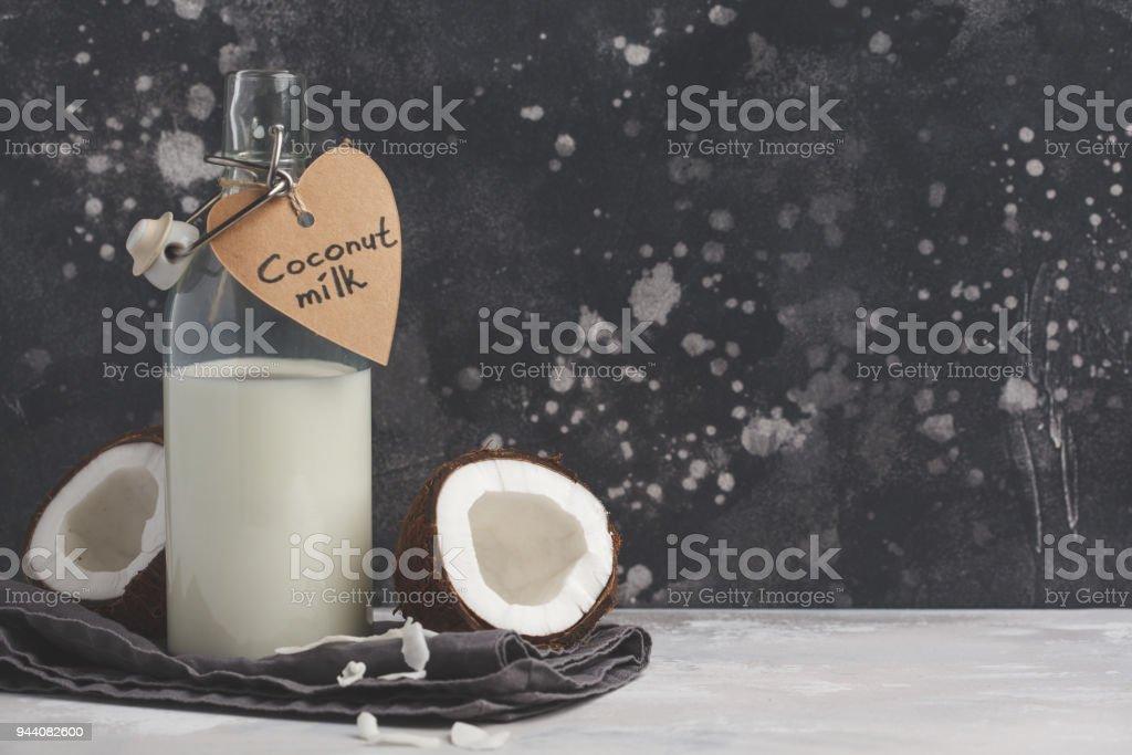 Vegan coconut milk non dairy in bottle, copy space, dark background. Vegan healthy food concept stock photo