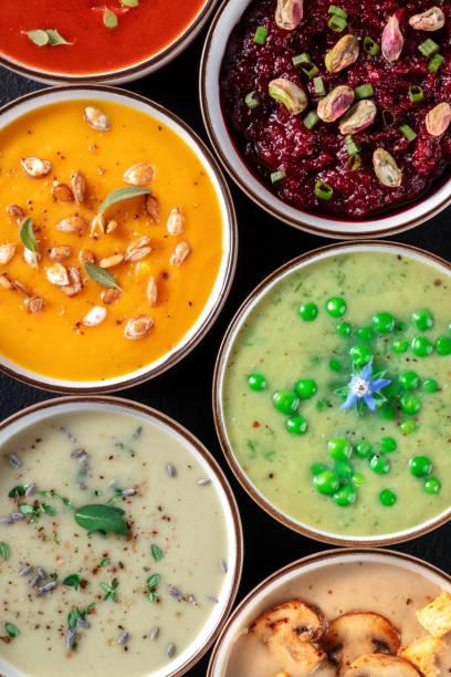 Vegan cream soups assortment. Various vegetable soups, shot from above stock photo