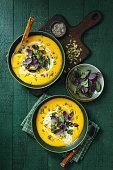 Vegan Creamy Roasted Pumpkin Soup on dark green background. Top view.