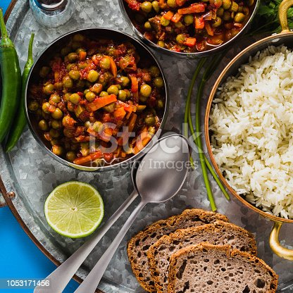 istock vegan curry with green peas and basmati rice served on a blue table tray, healthy Indian comfort food 1053171456