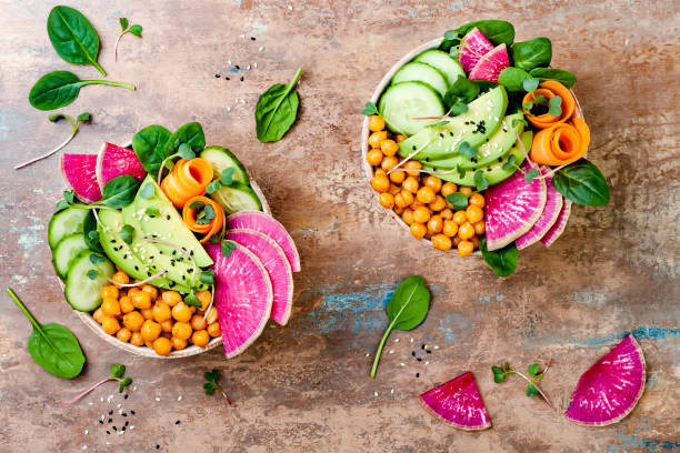 Vegan, detox Buddha bowl recipe with avocado, carrots, spinach, chickpeas and radishes. Top view, flat lay, copy space stock photo