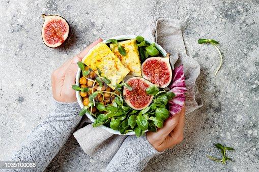 Vegan, detox Buddha bowl recipe with turmeric roasted tofu, figs, chickpeas and greens. Top view, flat lay