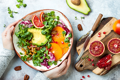 Vegan Detox Buddha Bowl With Turmeric Roasted Chickpeas Greens Avocado Persimmon Blood Orange Nuts And Pomegranate Top View Flat Lay Stock Photo - Download Image Now