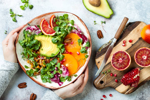 vegan, detox buddha bowl with turmeric roasted  chickpeas, greens, avocado, persimmon, blood orange, nuts and pomegranate. top view, flat lay - healthy food imagens e fotografias de stock