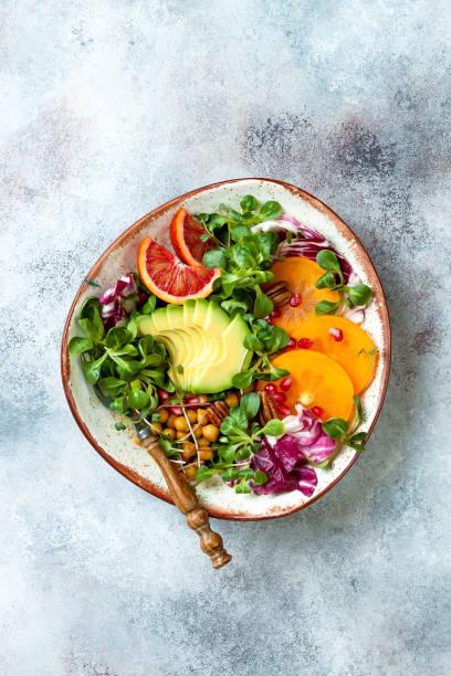 Vegane, entgiftete Buddha-Schale mit tränisch gerösteten Kichererbsen, Grüns, Avocado, Persimmon, Blutorange, Nüssen und Granatapfel. Top Aussicht, flach gelegen – Foto