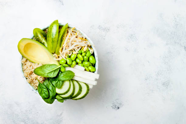 Vegan, detox green Buddha bowl recipe with quinoa, avocado, cucumber, spinach, tomatoes, mung bean sprouts, edamame beans, daikon radish. Top view, flat lay, copy space stock photo