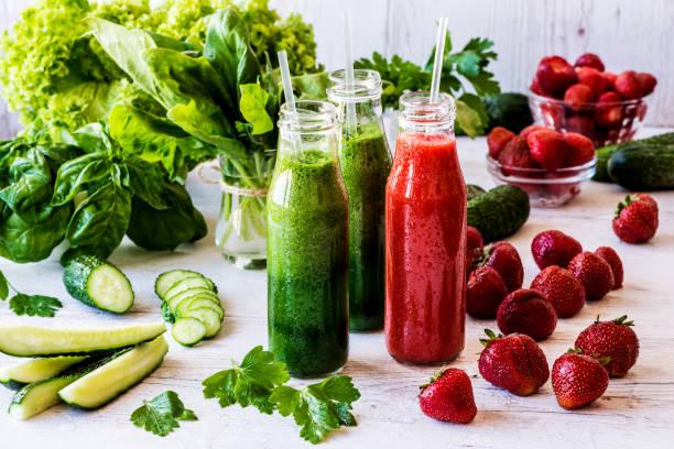 ビーガンのドリンク。新鮮な緑のスムージーと軽い木製の背景上の成分とイチゴのスムージー。健康的なデトックス飲み物。 - ローフード ストックフォトと画像