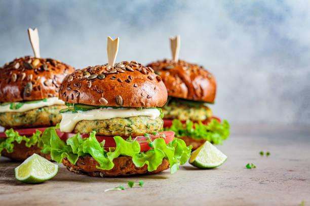 hamburguesa vegana de falafel con verduras y salsa, fondo oscuro, espacio de copia. concepto alimenticio saludable basado en plantas. - vegana fotografías e imágenes de stock
