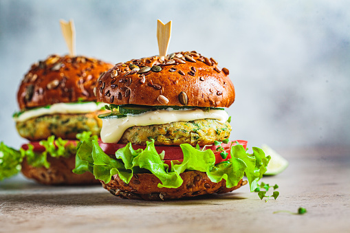 Vegan falafel burger with vegetables and sauce, dark background, copy space. Healthy  plant based food concept.